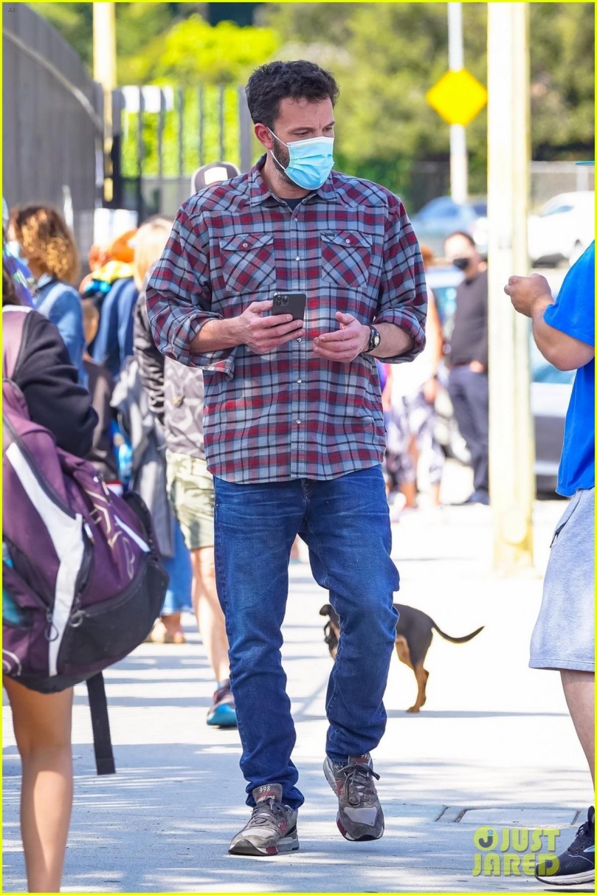 Nam diễn viên mặc áo sơ mi kẻ và quần jeans trẻ trung.