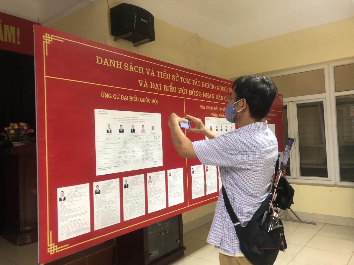 Cử tri chụp lại thông tin về người ứng cử đại biểu QH và HĐND các cấp.