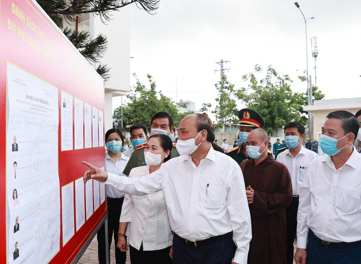 Chủ tịch nước Nguyễn Xuân Phúc và các ứng cử viên xem danh sách ứng cử viên ĐBQH khóa XV được niêm yết tại đơn vị bầu cử số 10.