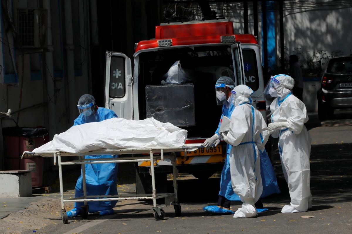 Nhân viên nhà xác đưa thi thể bệnh nhân Covid-19 lên xe cứu thương để tới nơi hỏa táng. Ảnh: Reuters