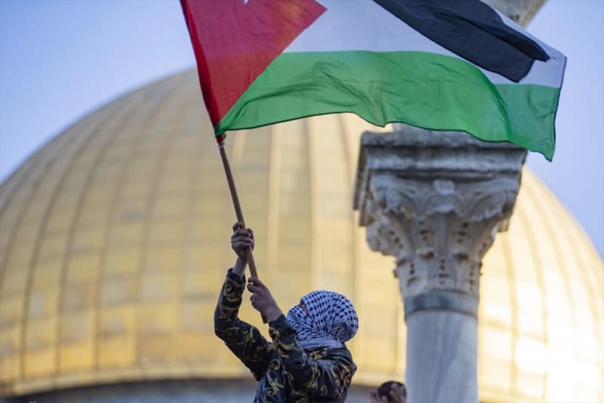 Người biểu tình vẫy cờ Palestine trong cuộc biểu tình sau lễ cầu nguyện Eid Al-Fitr tại khu phức hợp Nhà thờ Hồi giáo Aqsa ở Jerusalem ngày 13/5/2021. (Nguồn: Anadolu Agency / Mostafa Alkharouf).