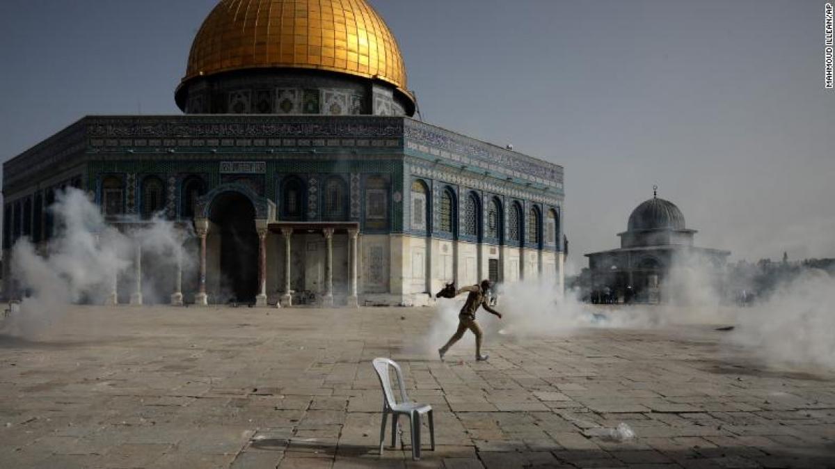 Một người đàn ông Palestine chạy khỏi làn đạn hơi cay trong cuộc đụng độ với lực lượng an ninh ở Đền thờ Al Aqsa. Ảnh: AP