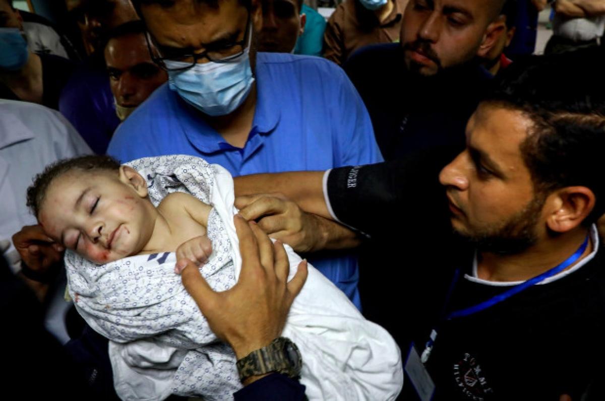 Em bé được cứu sống khỏi đống đổ nát trong khi nhiều người thân của em đều thiệt mạng sau cuộc không kích của Israel vào Trại tị nạn al-Shati. Ảnh: ZUMAPRESS.com