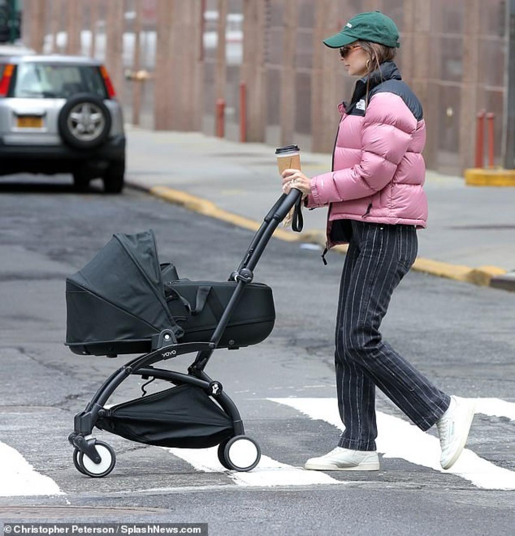 Người mẫu 9X mặc đồ ấm áp, cầm theo ly cafe nóng hổi và đẩy xe đưa con ra phố dạo chơi.
