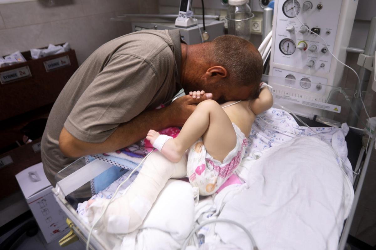 Cha của Omar là ông Mohammed al-Hadidi gục khóc sau khi em bé này được cứu sống khỏi đống đổ nát ở thành phố Gaza. Ảnh: APA