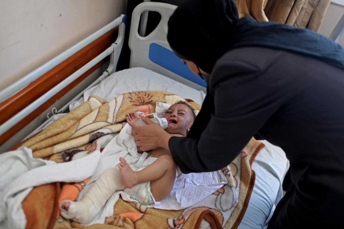 Một người phụ nữ cho em bé Omar Al-Hadidi uống sữa tại một bệnh viện ở Gaza. Ảnh: Reuters
