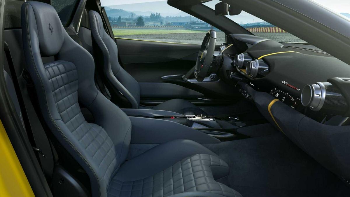 """Bước vào bên trong, khoang lái vẫn có thiết kế tương tự như 812 Superfast hay 812 GTS trước đây. Phần ốp cửa được thiết kế lại giúp giảm trọng lượng và ở bảng điều khiển trung tâm, """"H-gate"""" cần số dạng cần gạt mới sẽ có mặt để thay thế các nút vào số dạng bấm như trước. Ghế ngồi thể thao chỉnh tay cũng có được họa tiết bề mặt hoàn toàn mới, cổ điển và mang đậm tinh thần đua xe thể thao."""