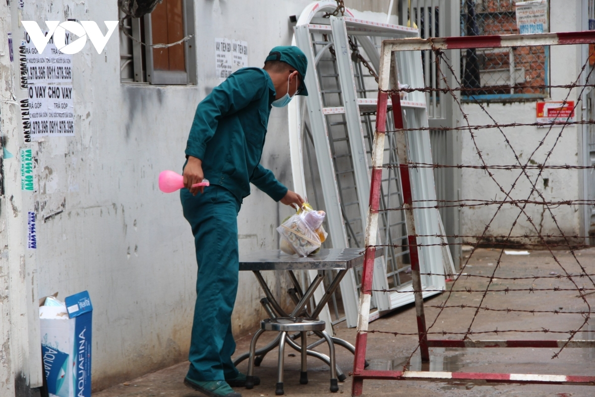 An on-duty official supports locals receive food deliveries in the alley where the mission's headquarters is based.