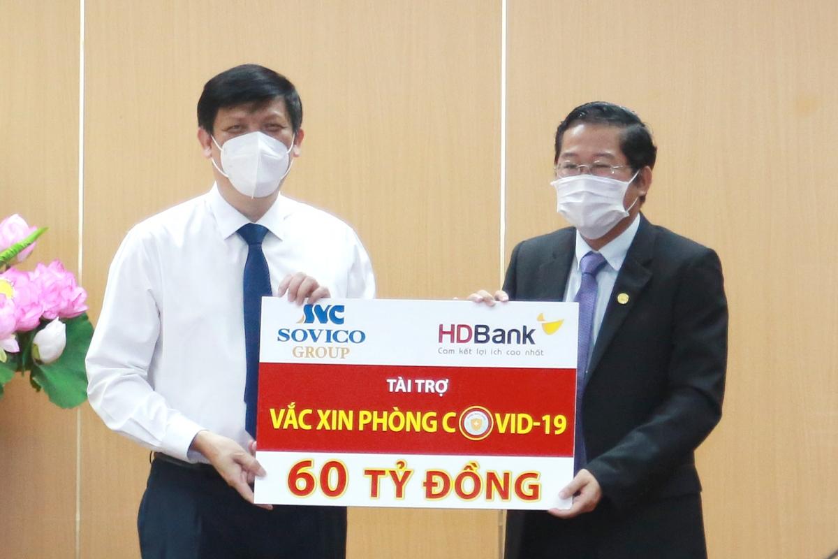 Ông Nguyễn Thanh Long - Bộ trưởng Bộ Y tế đại diện cho Bộ Y tế nhận nguồn kinh phí 60 tỷ đồng mua vaccine phòng Covid-19 do ông Phạm Quốc Thanh – Tổng Giám đốc HDBank đại diện HDBank và Sovico trao tặng.