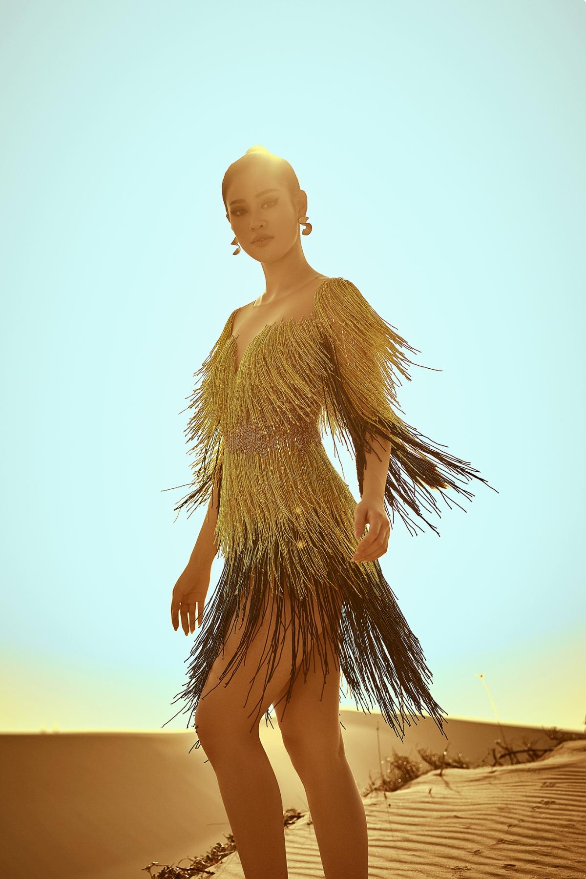 Trong trang phục đầm tua rua màu sắc rực rỡ, Khánh Vân nổi bật giữa đồi cát vào lúc bình minh, hoà quyện với khung cảnh tạo nên một bố cục hài hoà.