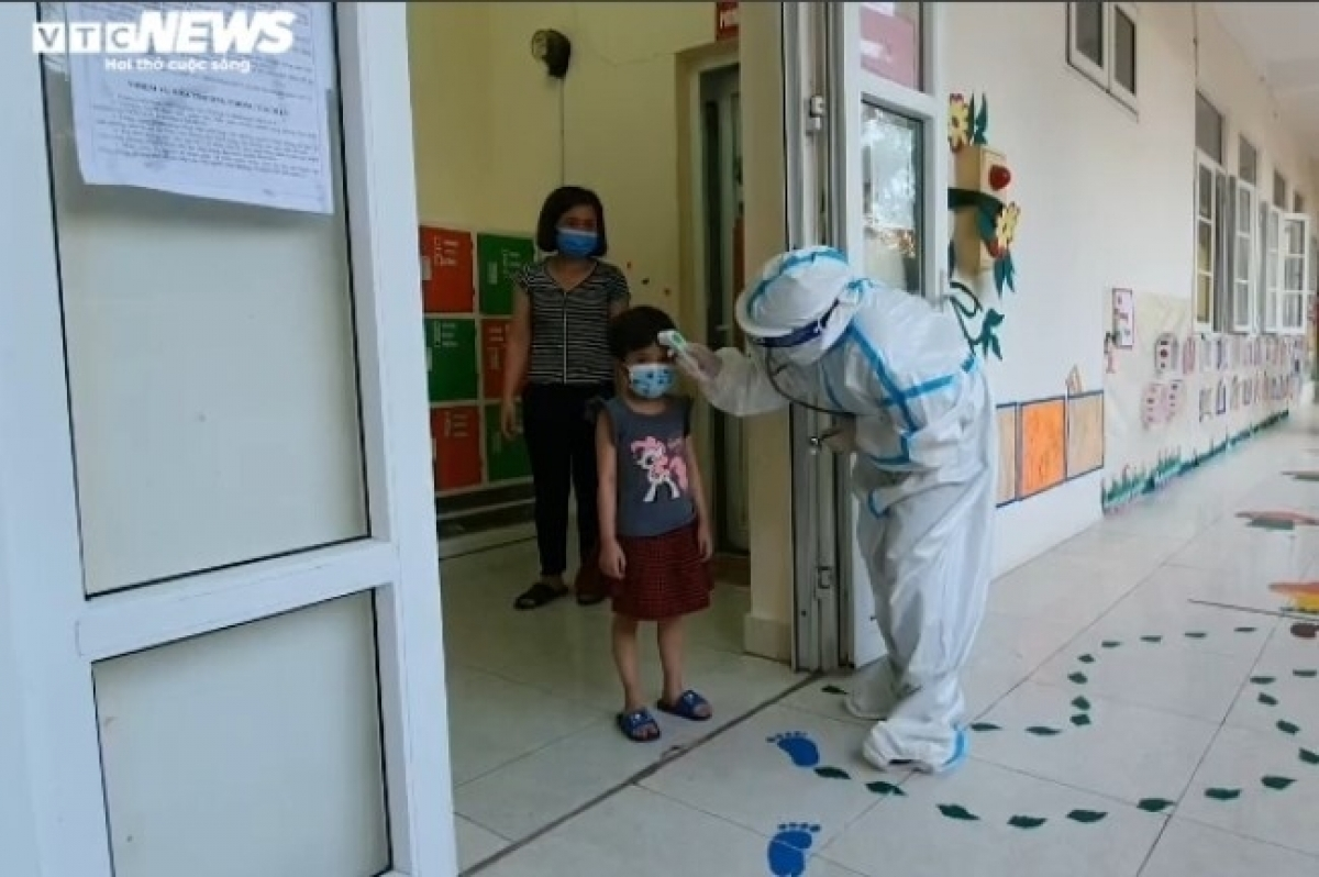 A healthcare worker measures the body temperature of the kids each day.