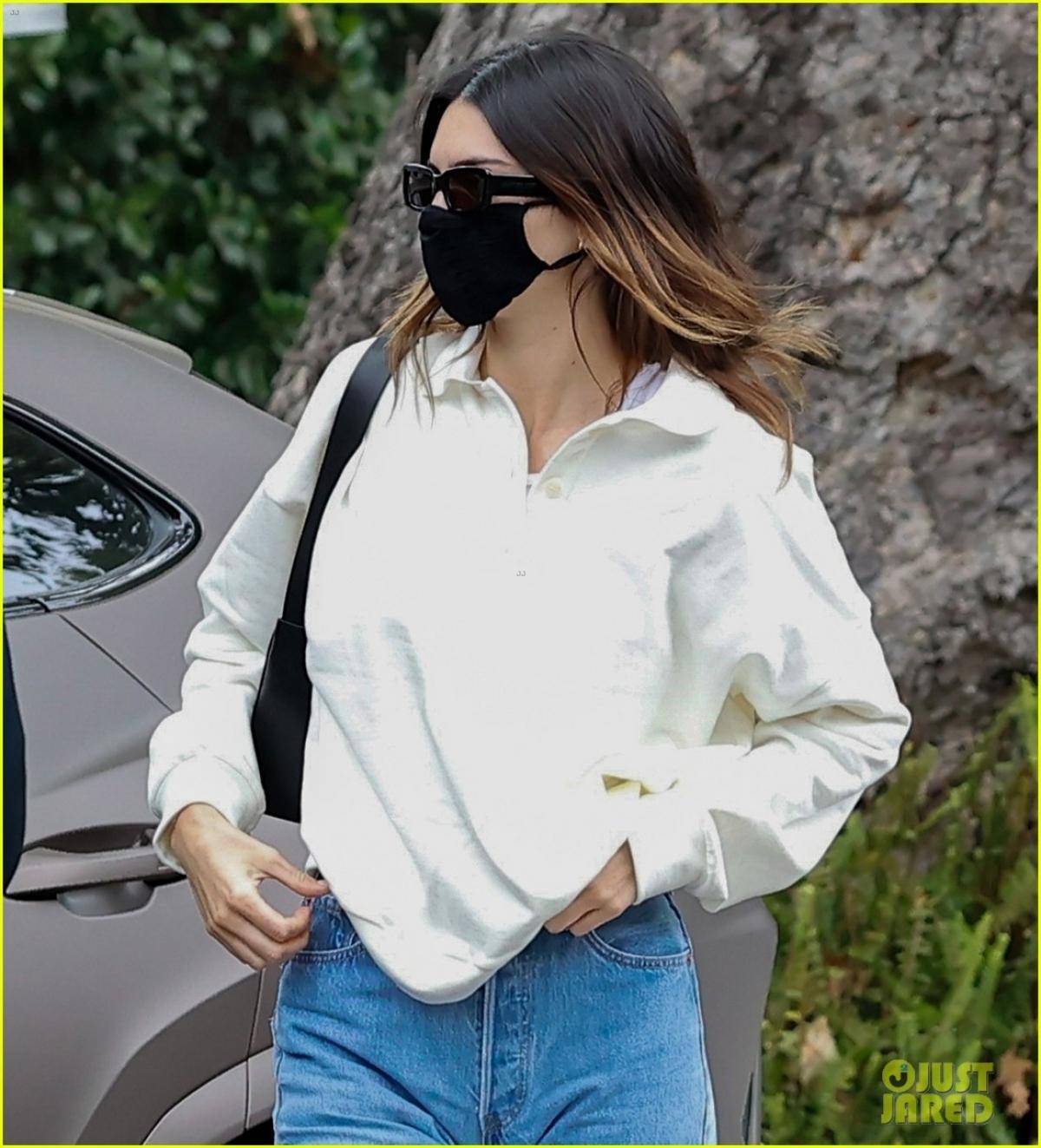 Em gái Kim Kardashian diện áo sơ mi và quần jeans trẻ trung. Cô buông xõa tóc và đeo khẩu trang cẩn thận ra phố.
