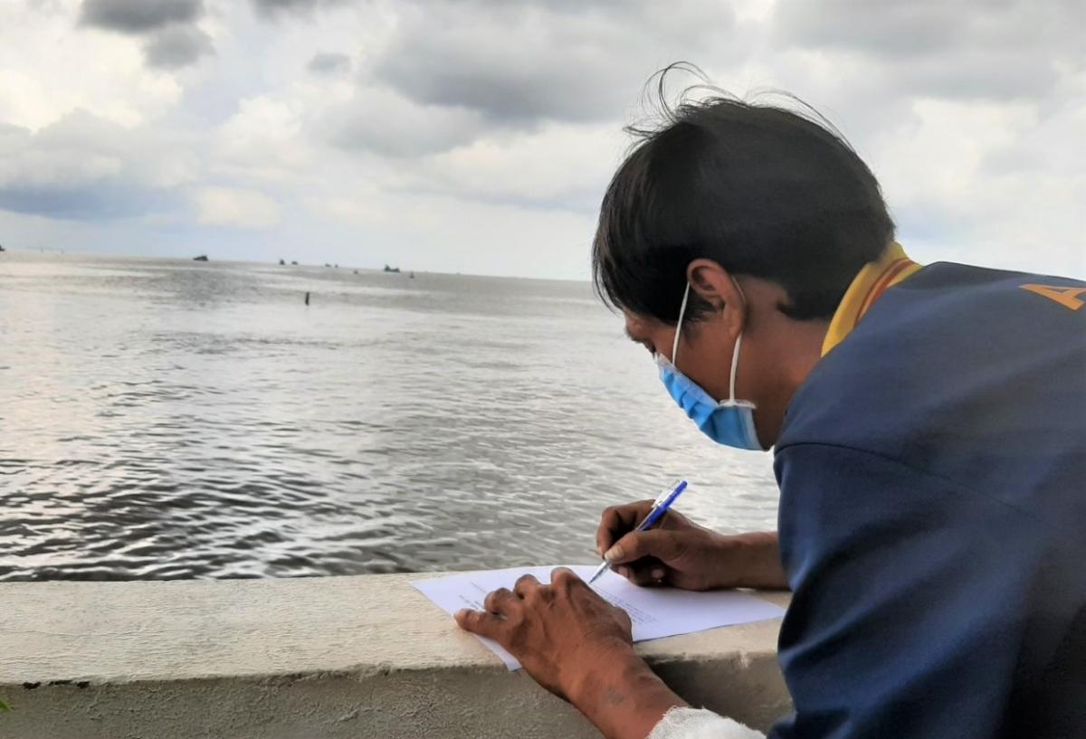 Ngư dân làm tờ khai báo y tế khi vào cửa biển Sông Đốc.