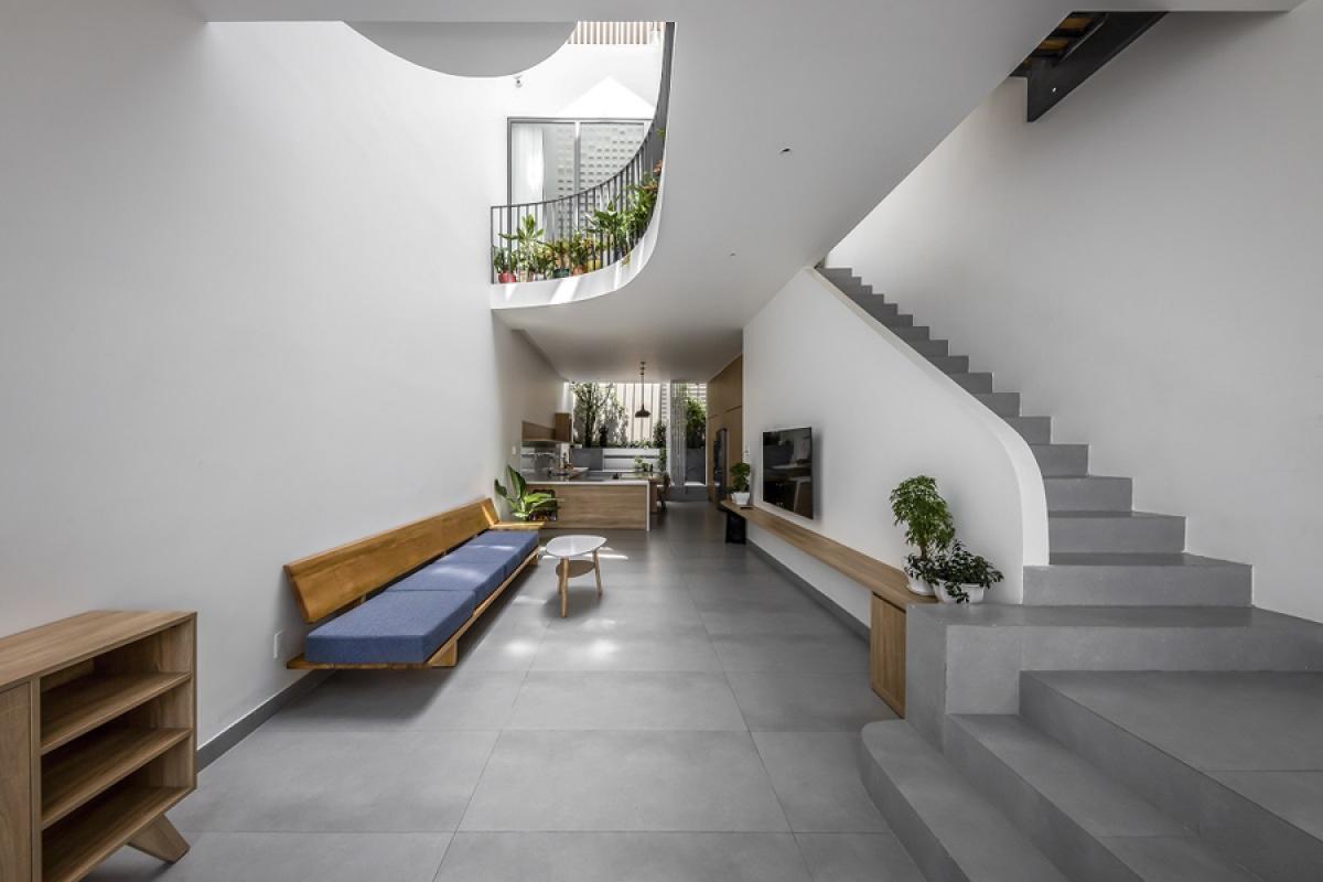 Tầng 1 là không gian phòng khách và bếp – phòng ăn liên thông với nhau suốt từ ngoài vào trong. Cầu thang lên tầng 2 trải dài nép sang một bên. Cầu thang này có cấu tạo bản bê tông xây gạch vừa để tận dụng gầm thang làm phòng WC, vừa mượn lan can làm bức tường để treo tivi. Để tạo cảm giác mát mẻ, màu trắng được sử dụng là màu chủ đạo kết hợp với màu xám và màu nâu sáng của gỗ. Đồ nội thất rất đơn giản phù hợp với phong cách kiến trúc hiện đại.