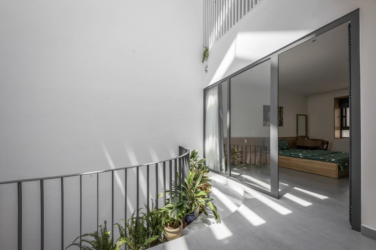 Phòng ngủ bố mẹ ở tầng 2 phía sau nhà mở ra giếng trời và hành lang bằng một vách kính lớn để kết nối không gian. Ánh nắng có thể chiếu vào tận trong phòng ngủ.