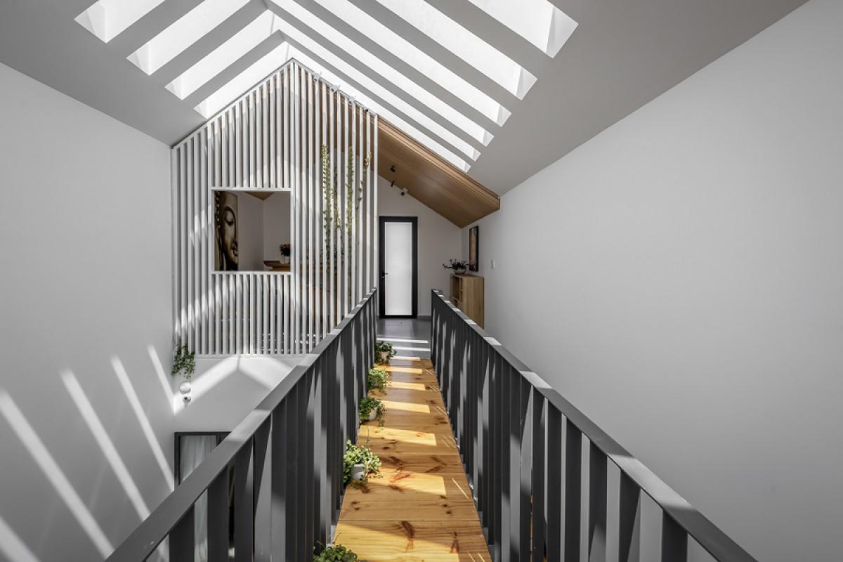 Cầu thang và hành lang thép – gỗ dẫn lên tầng 3 phía sau nhà. Nơi đây là phòng thờ kết hợp với thư viện. Bức tường phòng thờ được cấu tạo từ những nan thanh mảnh gợi cảm giác nhẹ nhàng và nhắc lại hình ảnh mặt tiền ngôi nhà với bộ mái dốc.