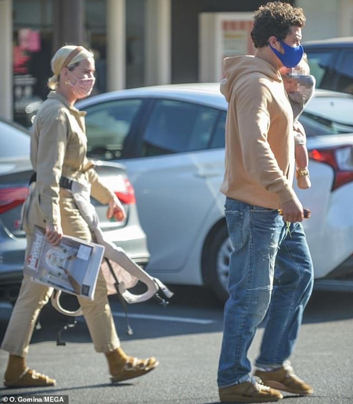 """Nam diễn viên phong độ, bế """"công chúa nhỏ"""" sải bước trên phố. Trong khi đó, Katy Perry bước theo phía sau."""