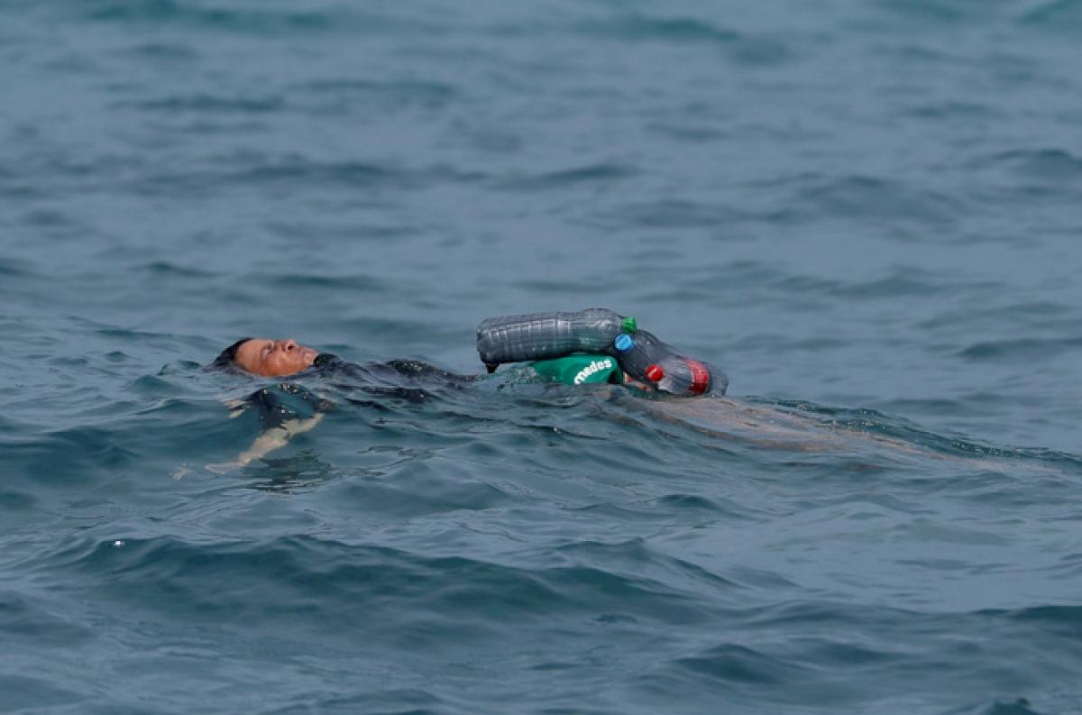 Thiếu niên Morocco buộc chai nhựa rỗng vào người để bơi qua biển đến vùng Ceuta. Ảnh: Reuters