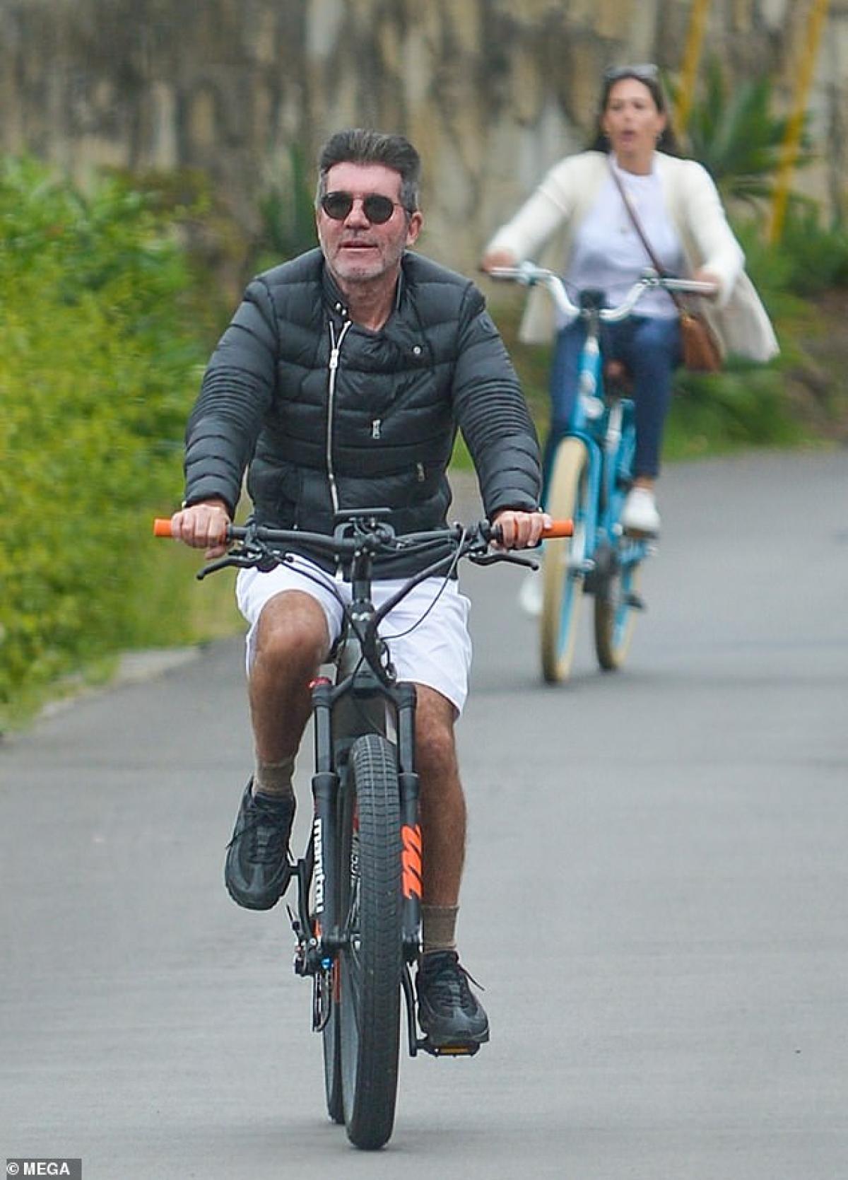 """Ngày 14/5, Simon Cowell hào hứng đạp xe cùng bạn gái Lauren Silverman ở California. """"Ông trùm truyền thông"""" gây chú ý với gu thời trang khác lạ khi mặc áo phao phối cùng quần shorts."""