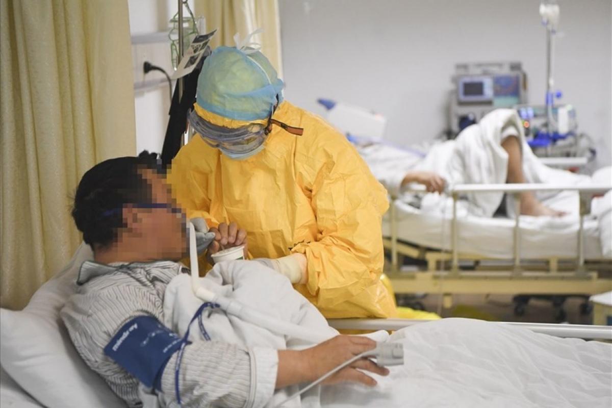 Bác sĩ giúp bệnh nhân Covid-19 uống nước trong phòng cách ly tại một bệnh viện ở Trung Quốc. Ảnh: Tân Hoa Xã.