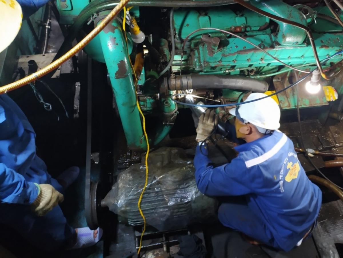 Nhân viên Trung tâm dịch vụ Hậu cần kỹ thuật đảo Sinh Tồn giúp ngư dân tàu cá QNg 90684 TS khắc phục sự cố.