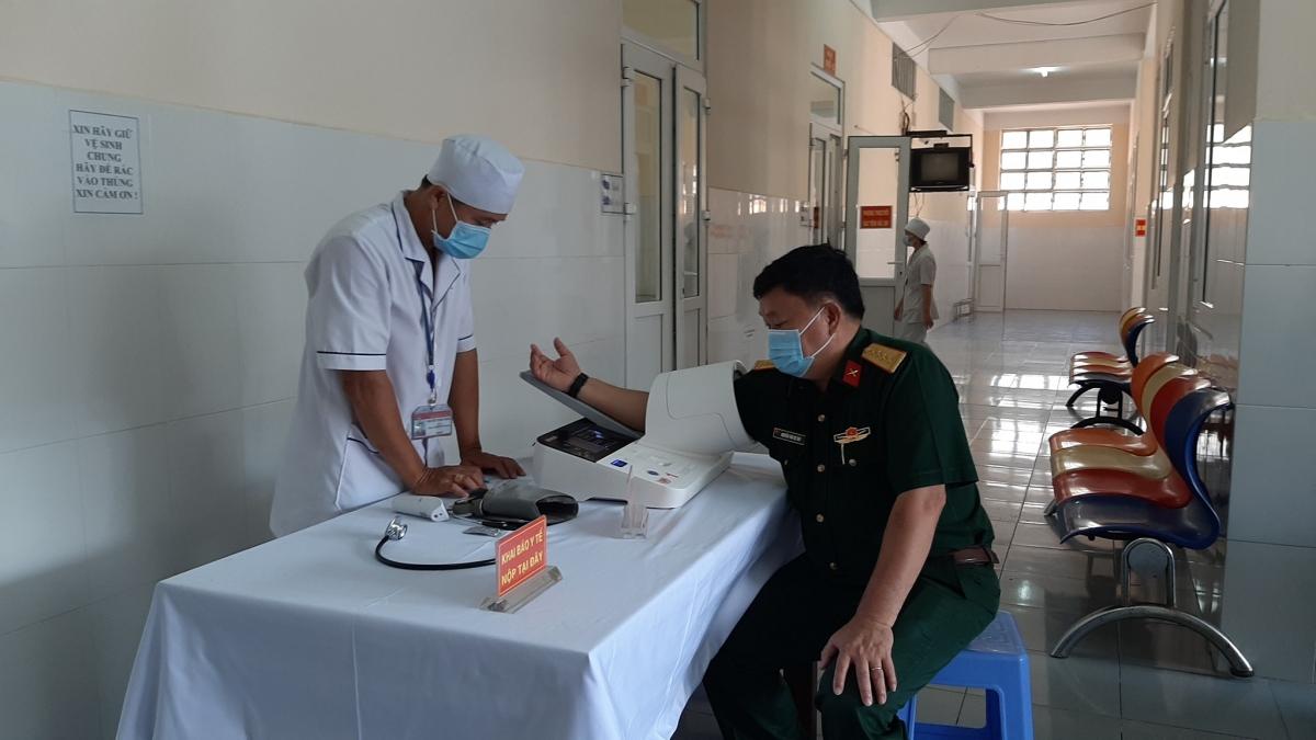 Cán bộ y tế kiểm tra sức khỏe trước khi tiêm phòng