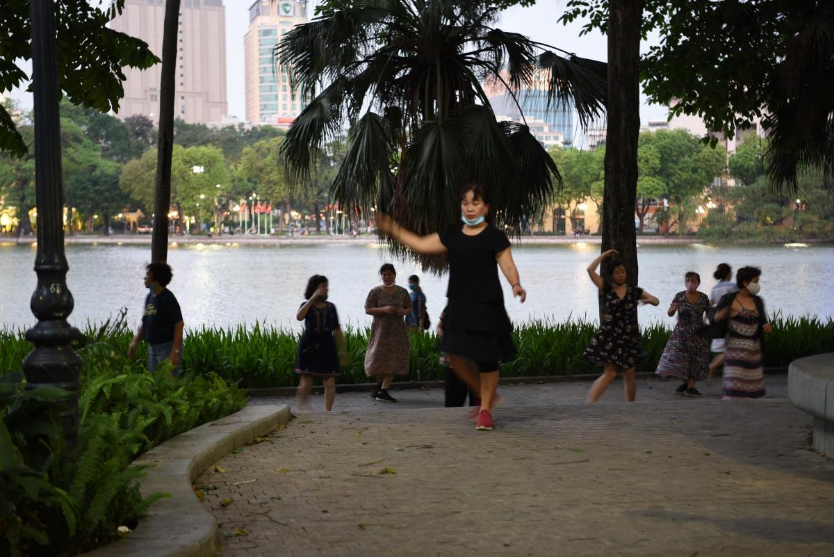 Bên bờ Hồ Gươm một nhóm phụ nữ thể dục nhịp điệu cũng không khẩu trang hoặc đeo không đúng cách.