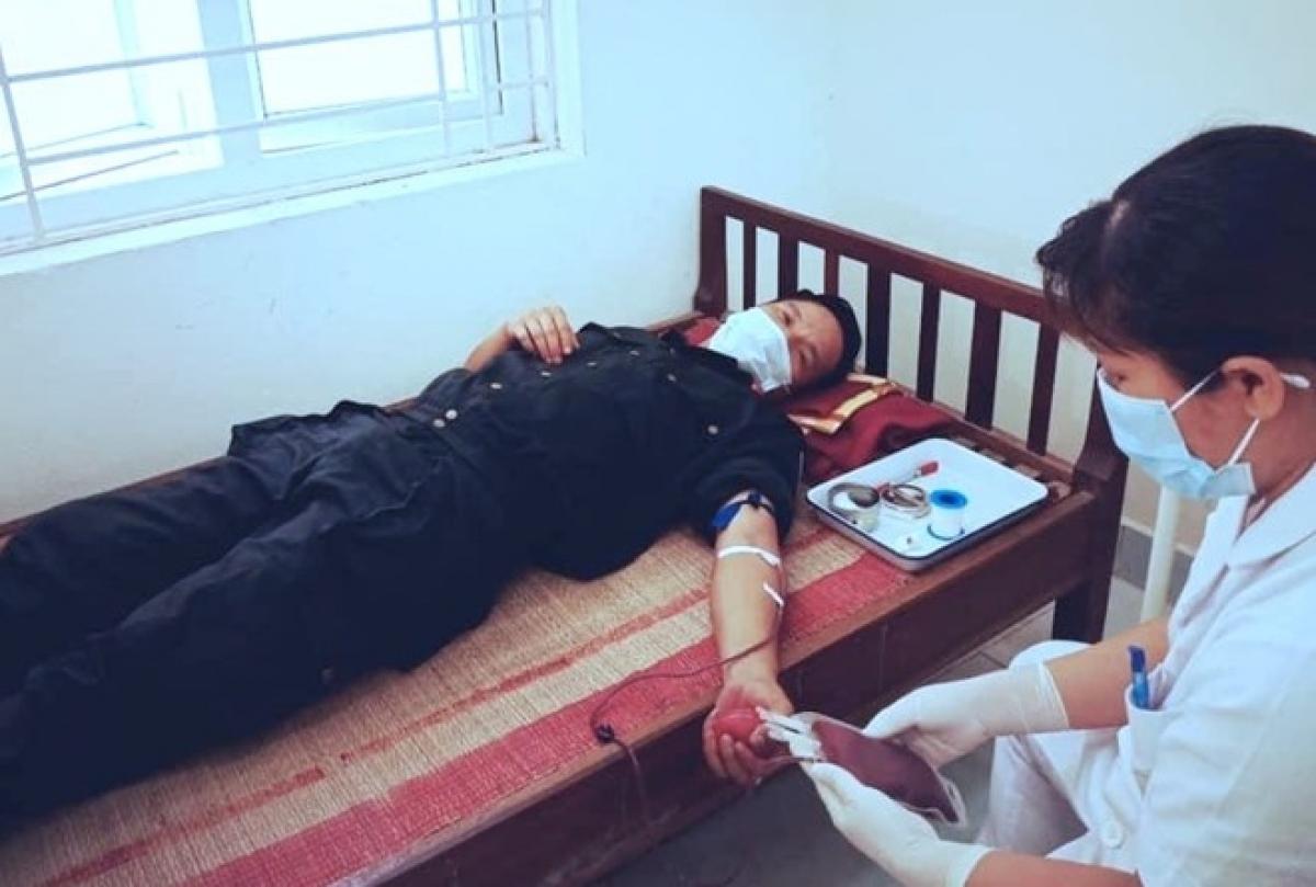 Thượng úy Lê Bá Tứ hiến 250ml máu nhóm O để truyền cho cháu Tùng. (Ảnh: CAND)