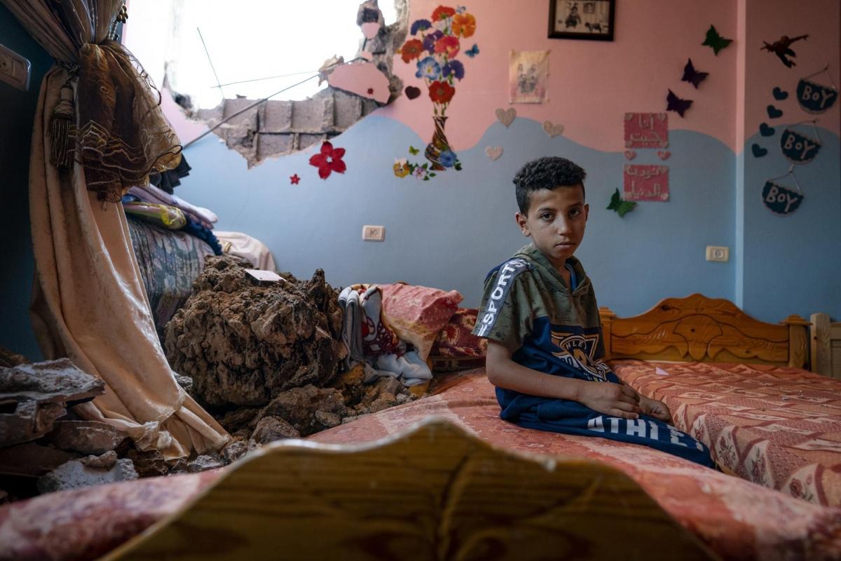 Cuộc chiến kéo dài 11 ngày giữa Israel và lực lượng Hamas đã gây ra thiệt hại nặng nề, khiếnhơn 250 người Palestine thiệt mạng, trong đó có hơn 60 trẻ em, và hơn 6.700 người bị thương. Trong ảnh:Ibrahim Al-Masri, 10 tuổi, ngồi trong phòng ngủ đã bị hư hại khi một cuộc không kích phá hủy tòa nhà lân cận.