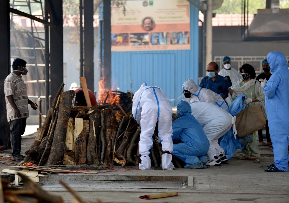 Nhân viên y tế và người nhà cầu nguyện lần cuối cho bệnh nhân COVID-19 xấu số trước lễ hỏa táng ở thủ đô New Delhi. (Ảnh: ANI)