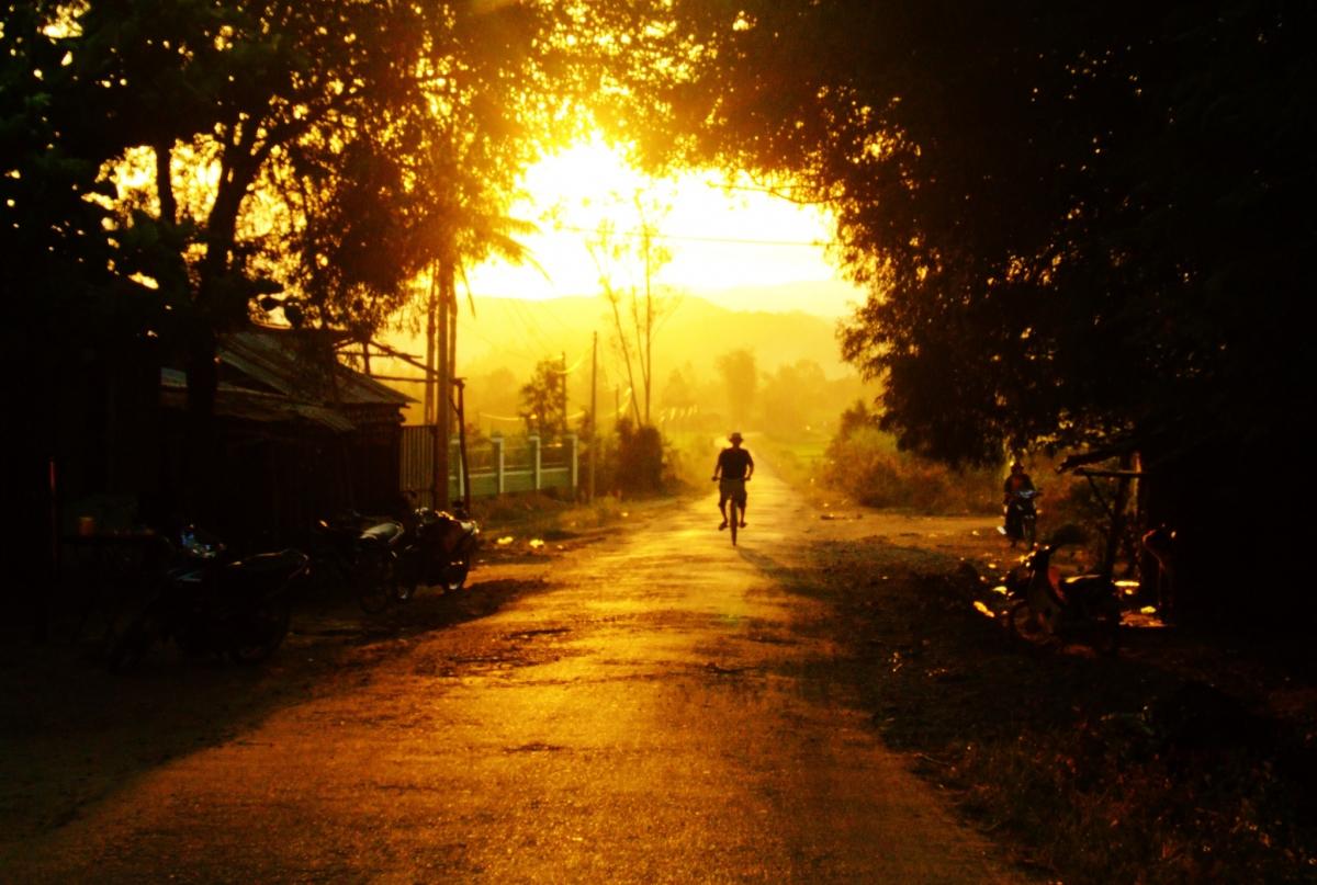Người đàn ông đạp xe đi thăm đồng về ở H.Đồng Xuân. Thời điểm này nắng chiều hắt lên những tia cuối cùng trong ngày rồi chìm khuất sau dãy núi phía xa. Khung cảnh mộc mạc, bình yên níu chân người.