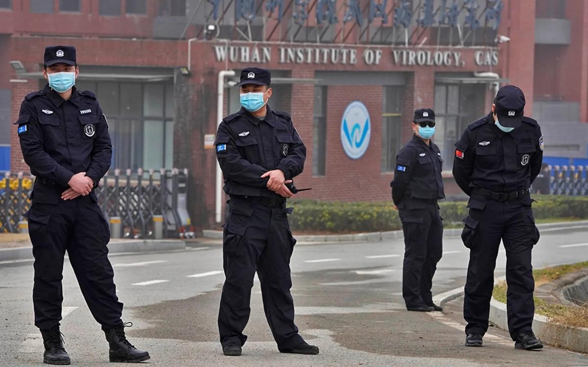 Các nhân viên bảo vệ xuất hiện trước trụ sở Viện Virus học Vũ Hán vào tháng 2/2021. Ảnh: AP.