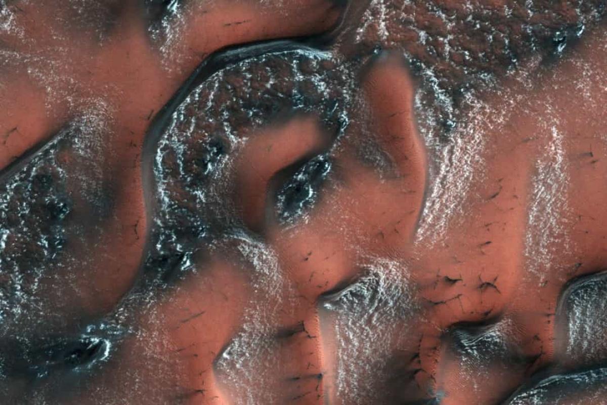 Những đụn cát ở bán cầu bắc của sao Hỏa được bao phủ bởi băng tuyết cho tới khi ánh nắng mùa xuân chiếu xuống khiến những lớp băng tan ra, để lộ lớp cát tối màu bên dưới những đụn cát.