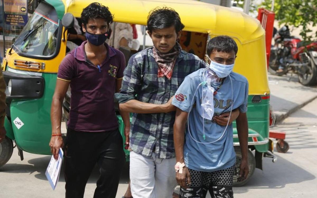 Người mắc Covid-19 được người thân đưa tới bệnh viện tại TP Ahmedabad, Ấn Độ, để điều trị. (Ảnh: AP)
