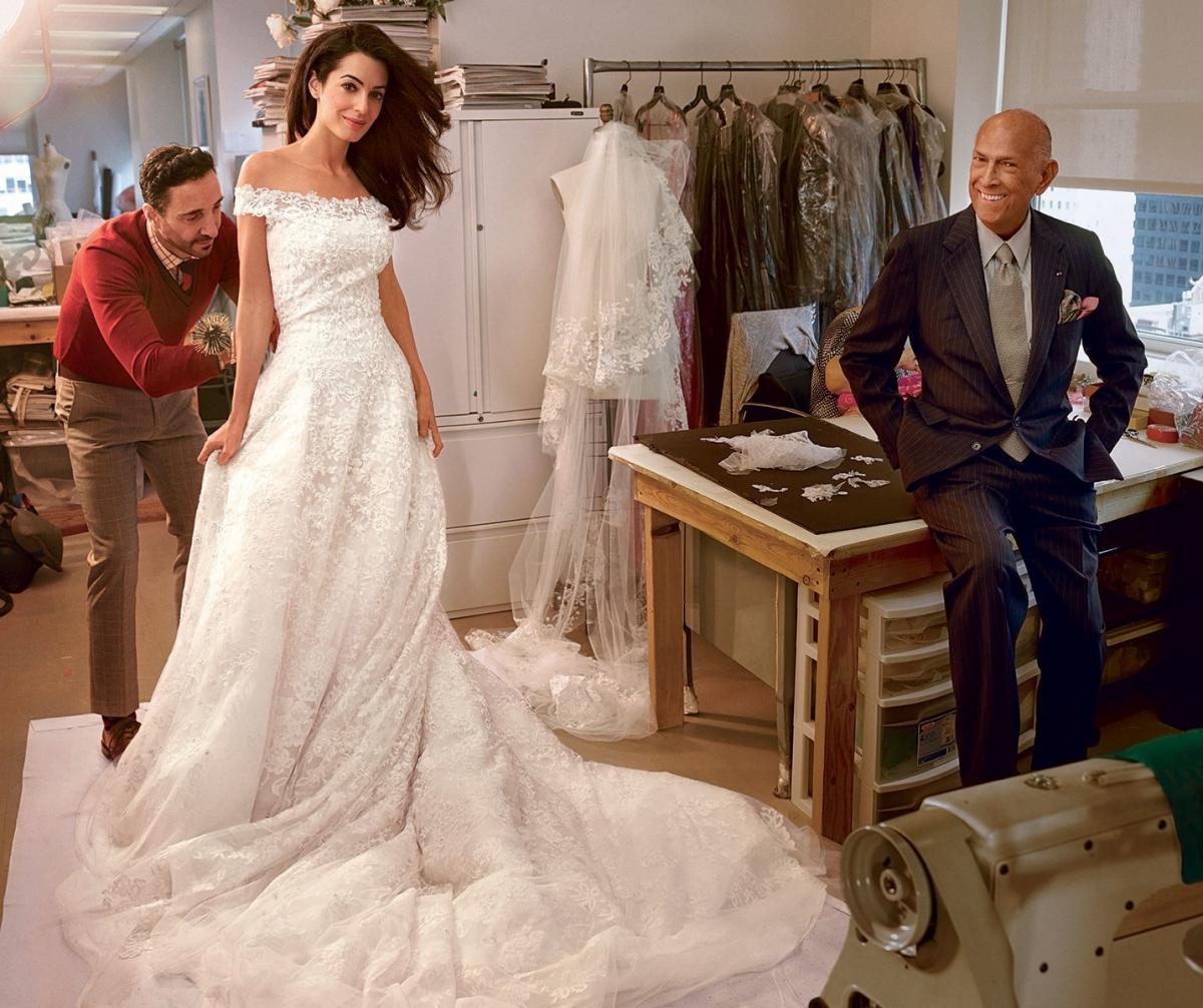 """Trước đám cưới năm 2014 với ngôi sao hạng A của Hollywood George Clooney, nữ luật sư xinh đẹp Amal Alamuddin đã đượcVoguechụp ảnhtrong buổi thử váy cuối cùng với nhà thiết kế quá cố Oscar de la Renta. Đây không chỉ là khoảnh khắc tuyệt đẹp không chỉ với Amal mà còn có ý nghĩa với giới thời trang. """"George và tôi muốn một đám cưới thật lãng mạn và trang nhã, và tôi không thể tưởng tượng được ai có thể hơn Oscar để nắm bắt được những điều tôi gửi gắm trong một chiếc váy"""", cô nói.""""Gặp anh ấy khiến quá trình thiết kế trở nên kỳ diệu hơn, vì anh ấy rất ấm áp và là một quý ông như vậy""""."""