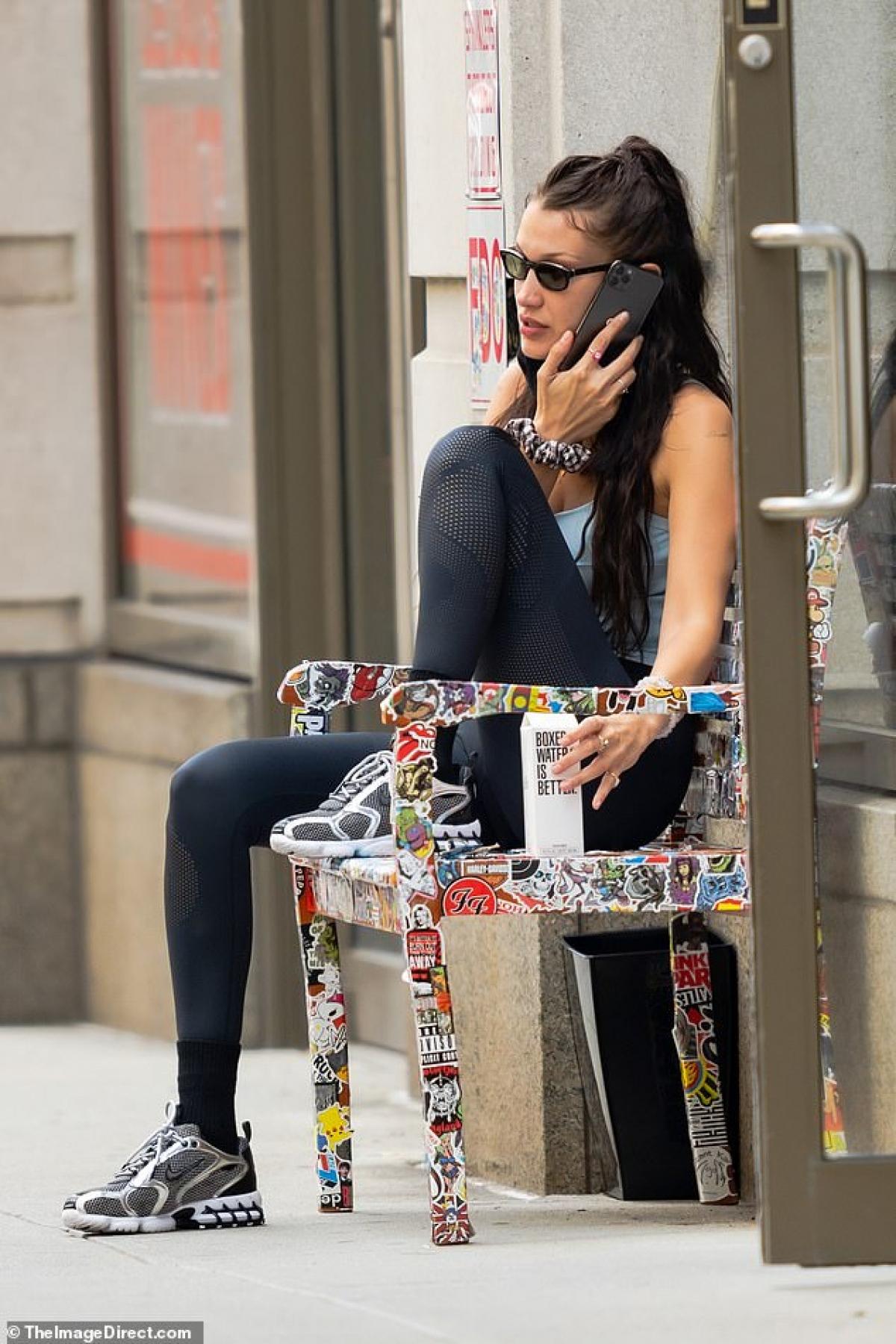 Cô tranh thủ ngồi trên ghế ngoài phố nghe điện thoại.