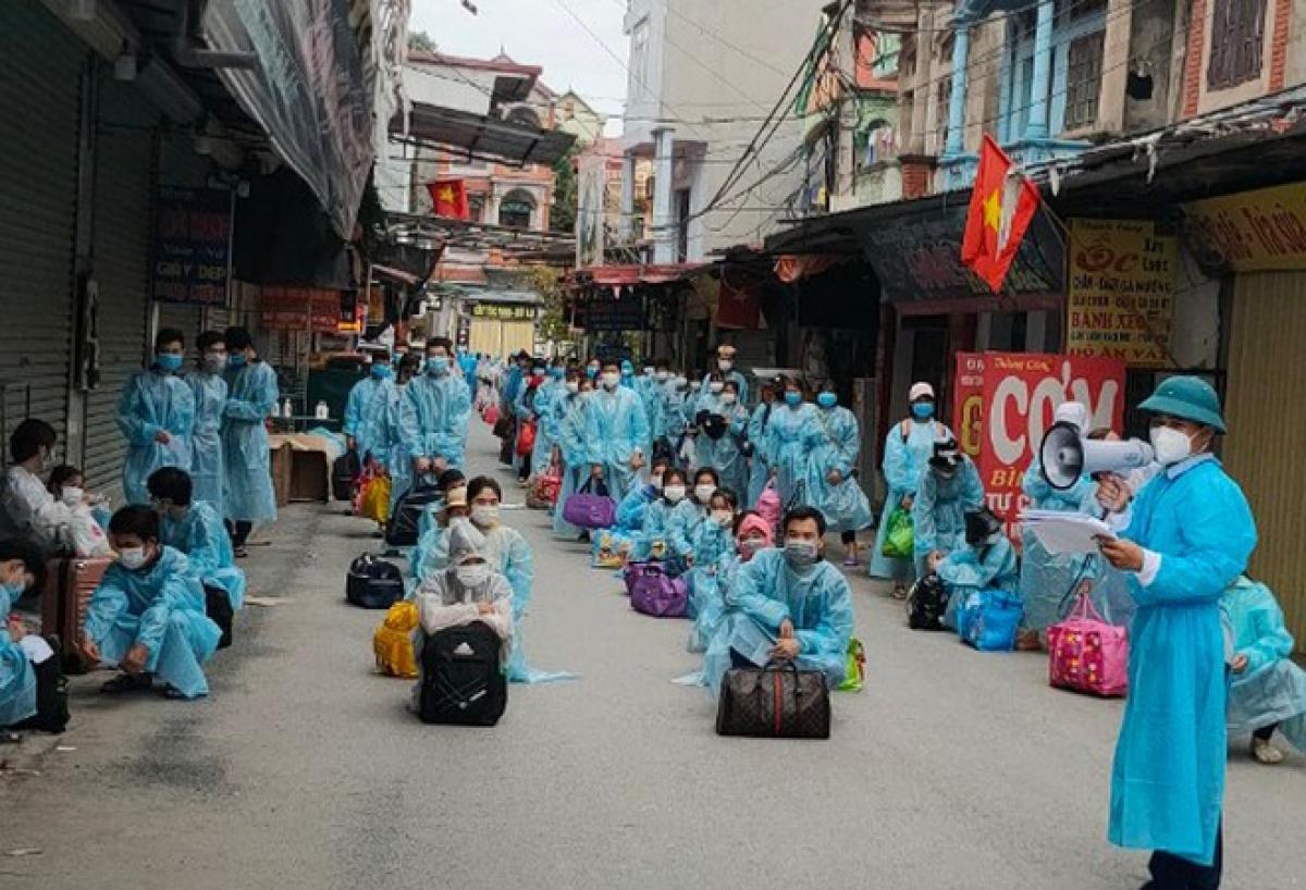 """Các công nhân trong trang phục bảo hộ đảm bảo phòng, chống Covid-19 di chuyển khỏi """"ổ dịch"""" thôn Núi Hiểu xã Quang Châu, huyện Việt Yên chiều ngày 5/6."""