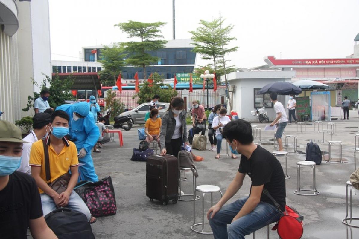 Công nhân ngồi đợi gọi tên lên xe ô tô trở về Sơn La trong sáng 12/6.