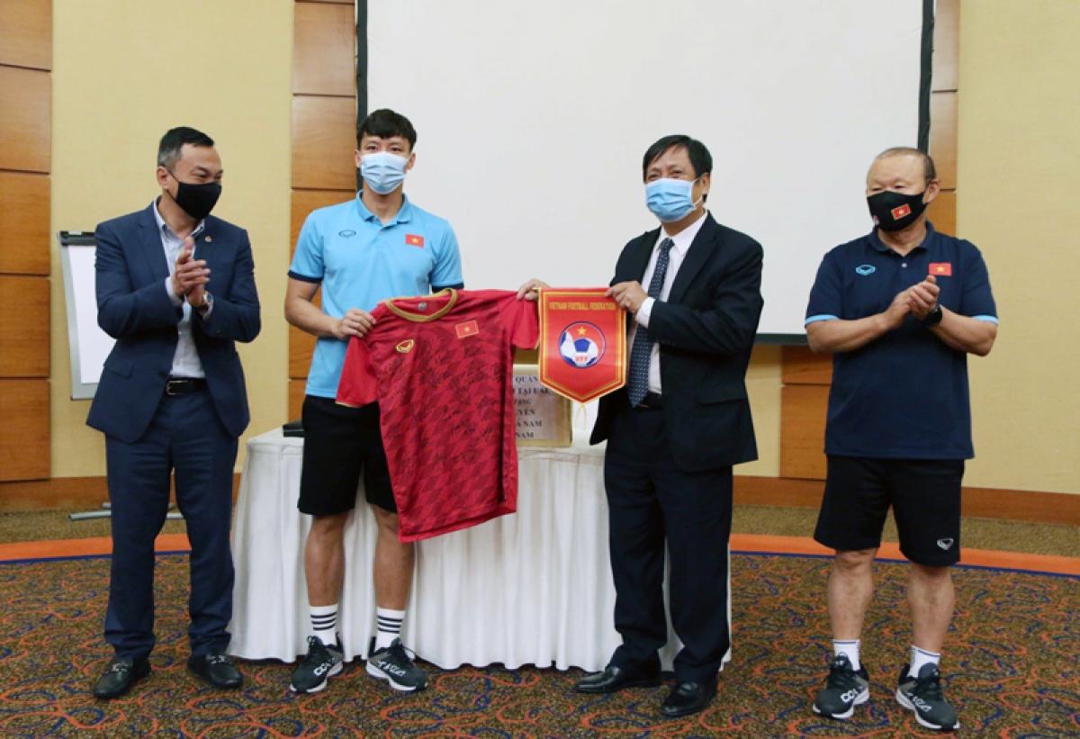 Đội trưởng Quế Ngọc Hải đại diện các cầu thủ đội tuyển tặng áo thi đấu, cờ lưu niệm cho Đại sứ Nguyễn Mạnh Tuấn (Ảnh: VFF).