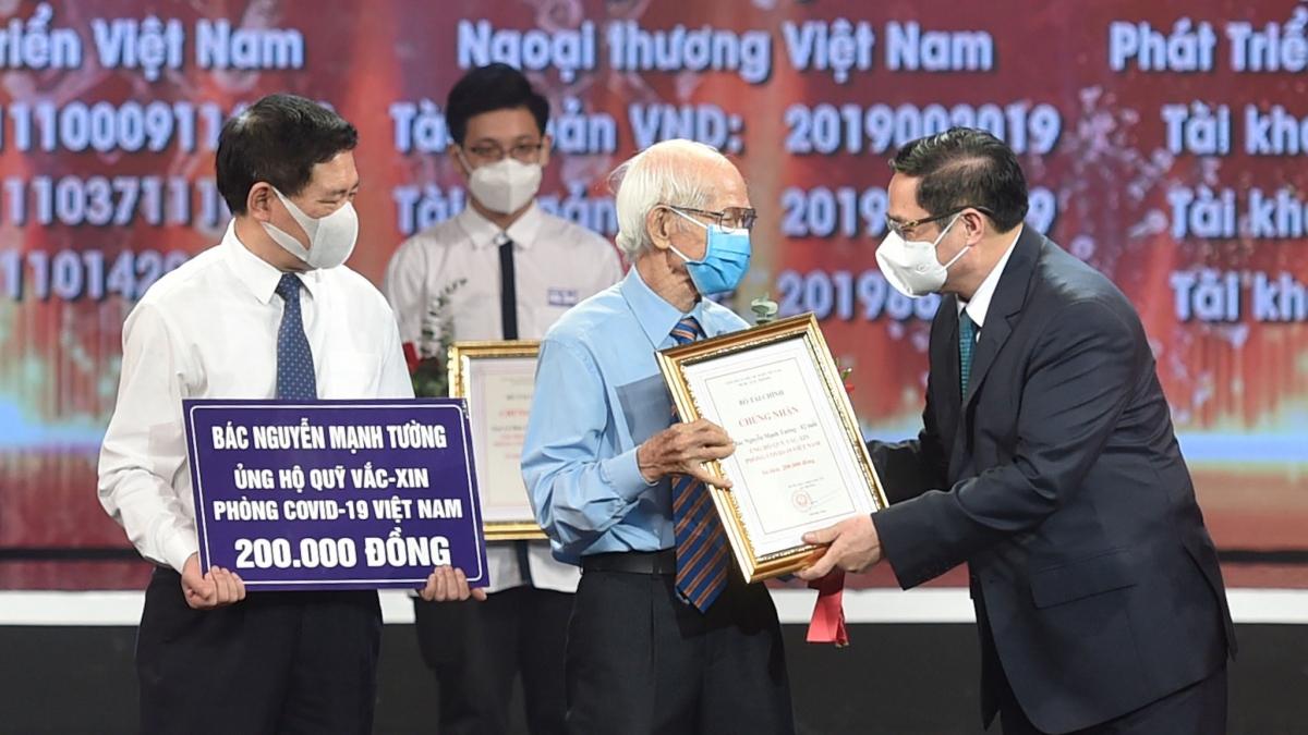 Thủ tướng Chính phủ Phạm Minh Chính trao chứng nhận, hoa cảm ơn bác Nguyễn Mạnh Tường, 82 tuổi, cán bộ hưu trí ngành đường sắt tại lễ ra mắt Quỹ vaccine phòng, chống Covid-19. (ảnh: Chinhphu.vn)