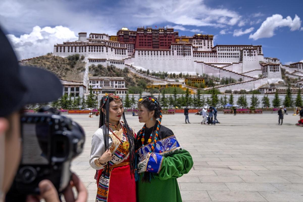 Du khách chụp ảnh với phông nền là cung điện Potala ở Lhasa. Nguồn: AP