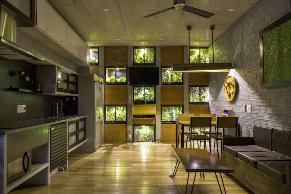 Phòng khách và phòng bếp ăn được tích hợp chung một không gian, nhìn ra những ô cửa xanh là bồn cây phía trước.