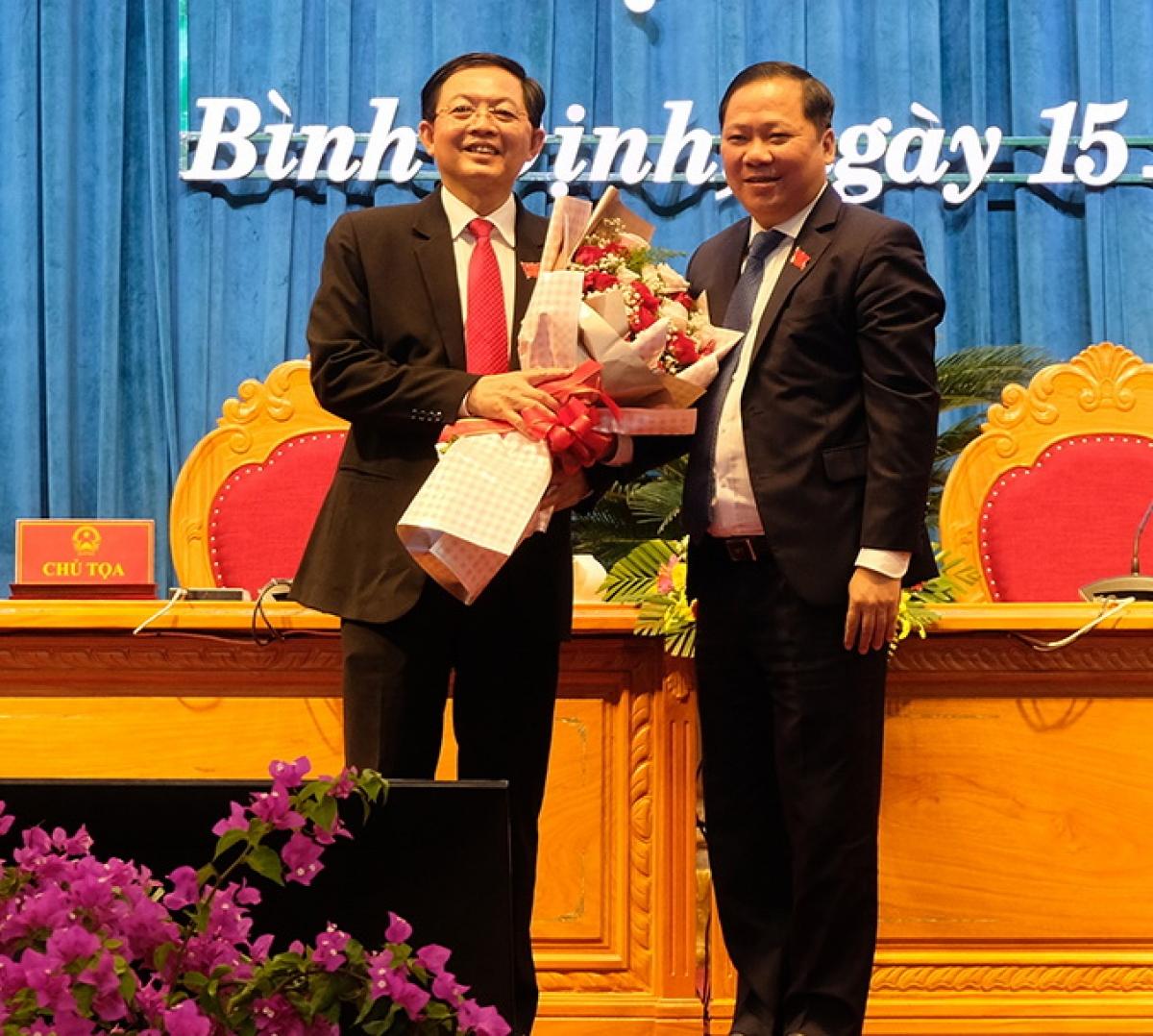 Ông Nguyễn Phi Long, Chủ tịch UBND tỉnh Bình Định (bên phải) tặng hoa ông Hồ Quốc Dũng, Bí thư Tỉnh ủy vừa được bầu lại làm Chủ tịch HĐND tỉnh khóa XIII