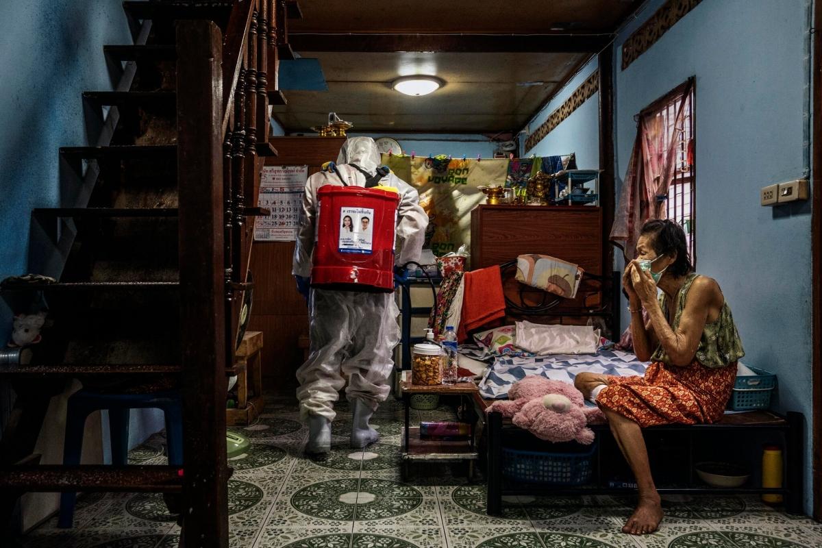Một công nhân phun khử khuẩn tại nhà một người dân dương tính với SARS-CoV-2 ở khu Khlong Toey. Ảnh: New York Times