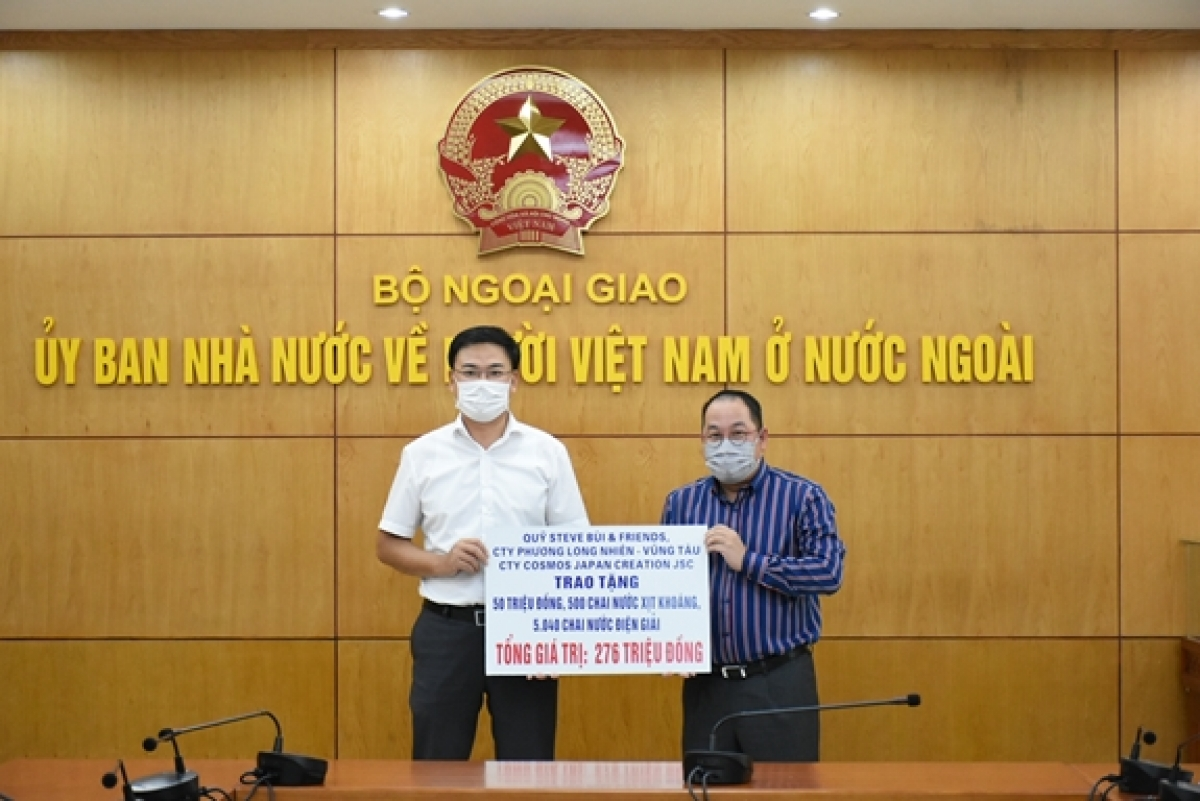Deputy Foreign Minister Pham Quang Hieu (left) receives money and medical supplies from overseas businesses in support of COVID-19 fight at home (Photo:qdnd.vn)
