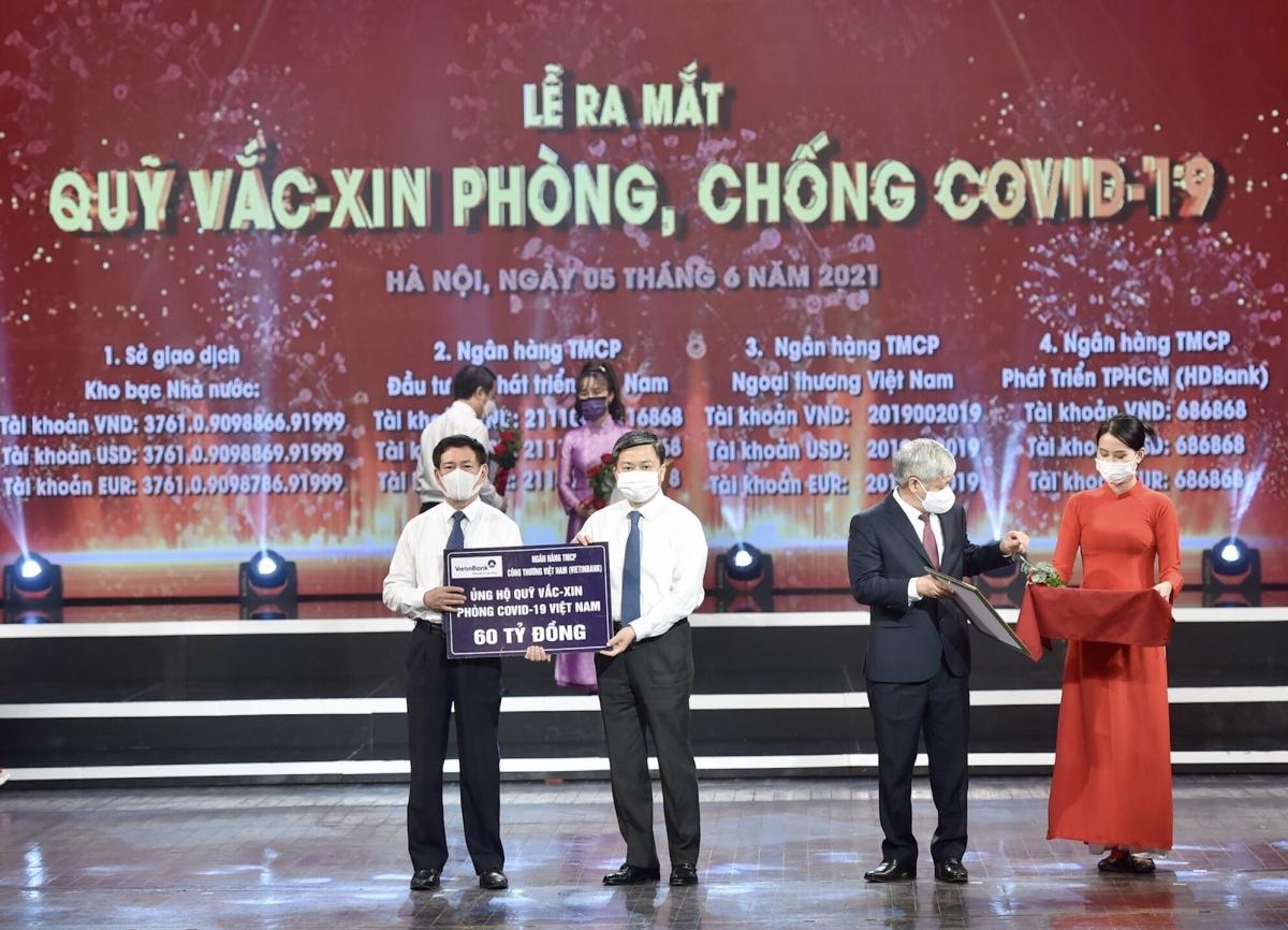 Ông Lê Đức Thọ - Ủy viên BCH Trung ương Đảng, Bí thư Đảng ủy, Chủ tịch HĐQT VietinBank (thứ 2 từ trái sang)trao tượng trưng kinh phí 60 tỷ đồng để đóng góp vào Quỹ Vaccine phòng chống Covid-19. (Ảnh: Duy Linh - Báo Nhân dân).