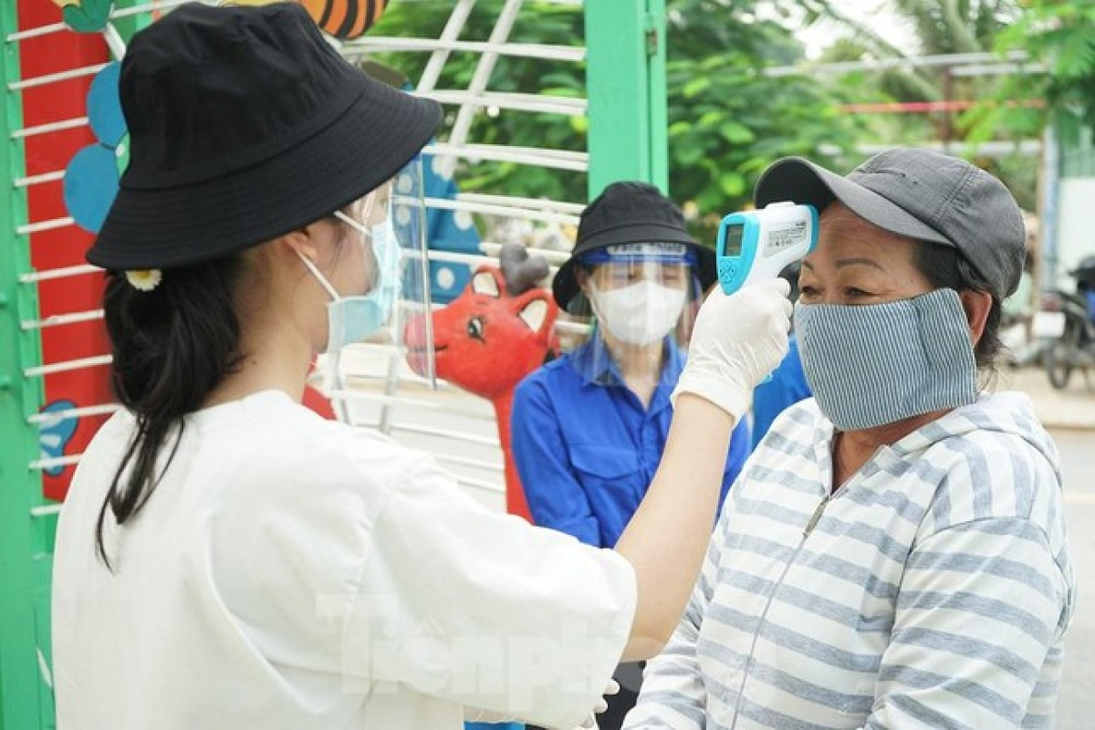 Local people have their body temperature measured, use hand sanitizer, and maintain a two-metre distance in order to prevent the potential spread of COVID-19.