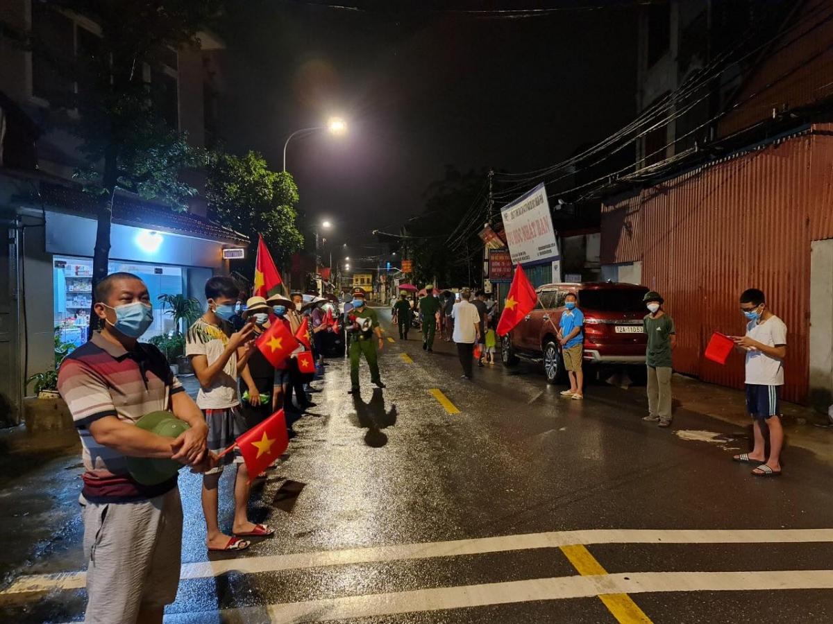 Người dân phấn khởi mang cờ ra vẫy dù trời đêm qua có mưa to.