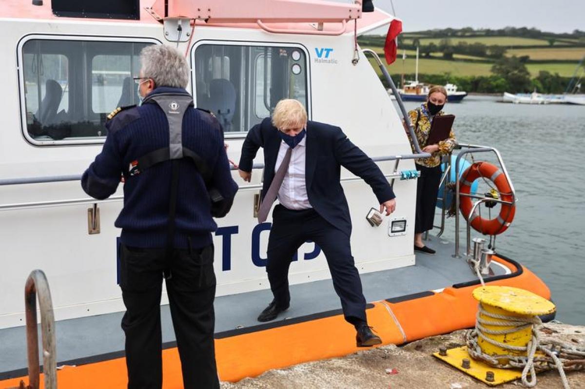 Thủ tướng Anh Boris Johnson xuống thuyền khi ông đến thăm xưởng Scott Woyka ở Falmouth, Cornwall, Anh. Ảnh: Reuters