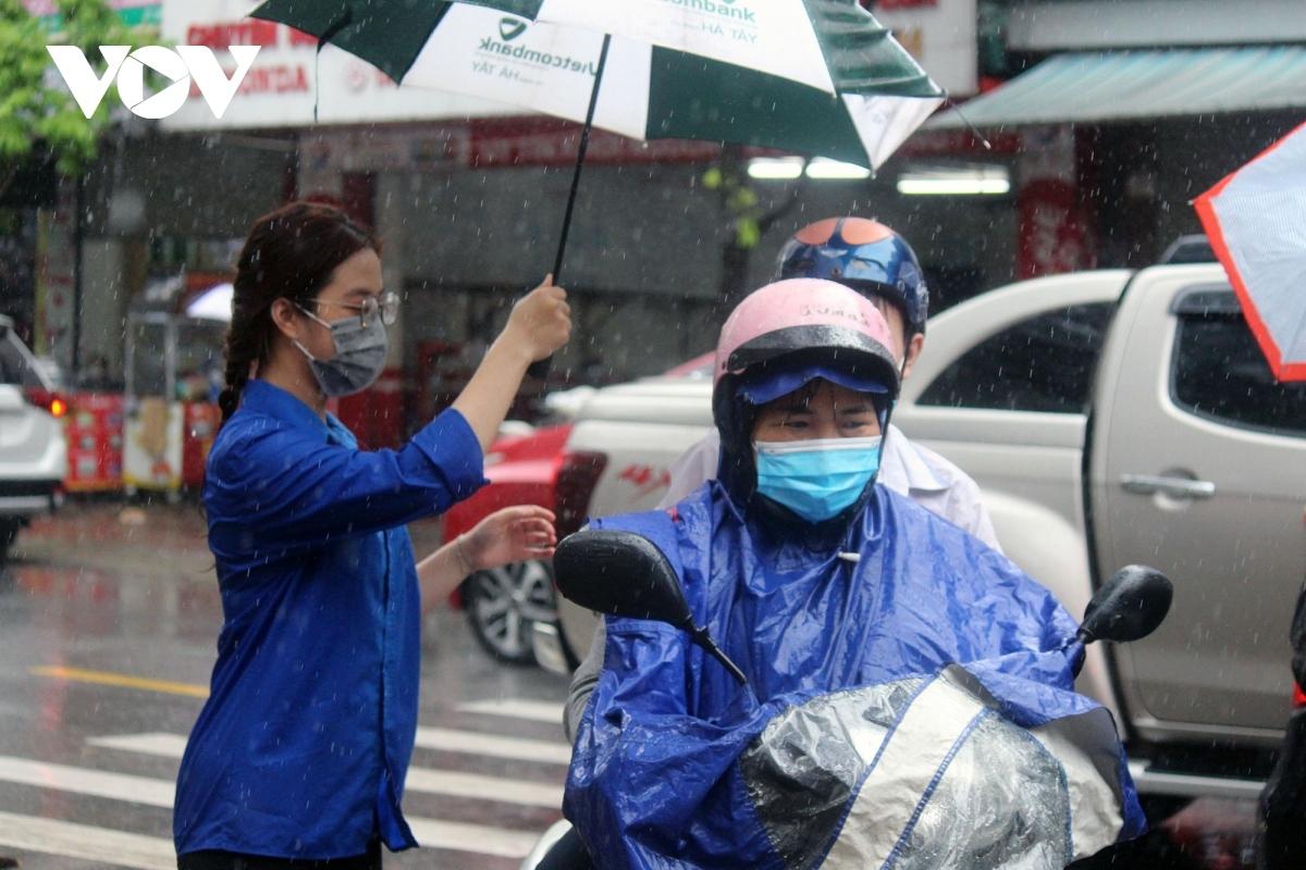 Những tình nguyện viên ướt đẫm áo do mưa vẫn nhiệt tình hỗ trợ, đưa thí sinh vào phòng thi an toàn.